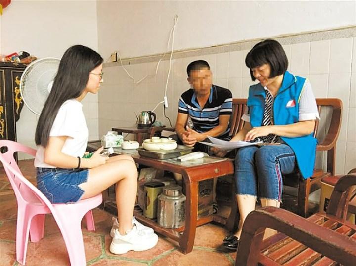 工作人员和志愿者上门详细登记贫困学子家庭情况